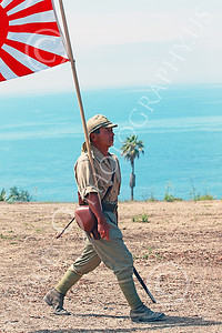 HR-WWIIIJS 00023 A World War II Imperial Japanese Army soldier marches proudly with a Pacific Ocean background while carrying the Japanese rising sun flag, historical re-enactor picture by Peter J Mancus