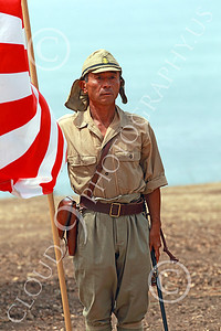 HR-WWIIIJS 00031 A World War II Imperial Japanese Army soldier with sword stands at attention with the  Japanese rising sun flag with the Pacific Ocean in the background, historical re-enactor picture by Peter J Mancus