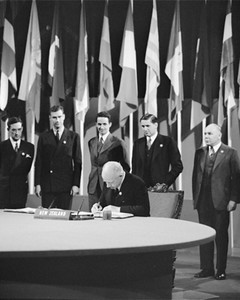 New Zealand Prime Minister and Minister of External Affairs and Chairman of the delegation Peter Fraser signs the UN Charter in San Francisco, 26 June 1945. Far right: Alister McIntosh. Credit: UN photo / McLain