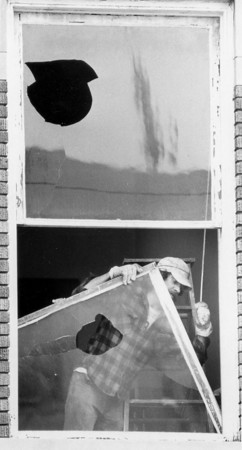 Photo by Brian Reynolds. John Irick-employee of F.D. Miller and Co.- which owns the building-takes out a broken window above the Video Connection at 109 S. Main, across from courthouse. April 1987