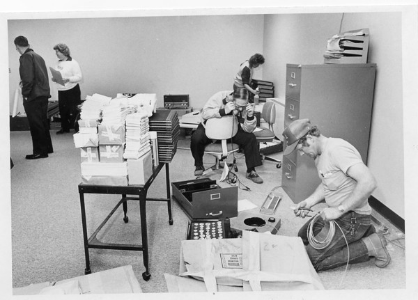 Photo by Brian Reynolds. 4/16/87. Indiana Bell employees Neal Givens (far right) and Bob Clary set up phone service in the temporary sheriff office.