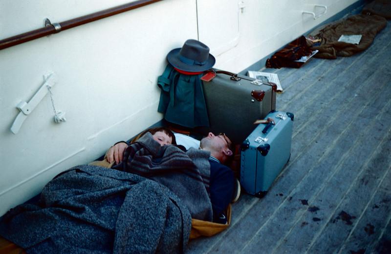 En sliten far har bygget et lite soverom av kofferter for seg og ungen. Herlig enkelt! Ut fra soveposene i bakgrunnen var han ikke alene om behovet for å sove litt.<br /> - Fra Ørnulfs reise i Nord Norge i '58 eller '59.