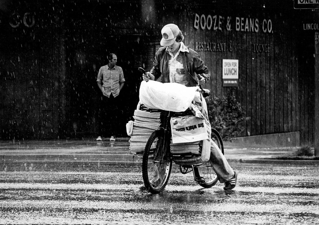. MAY 29 1981 - A paper boy crosses Lincoln St. in Denver despite a rain shower. (Denver Post file photo)