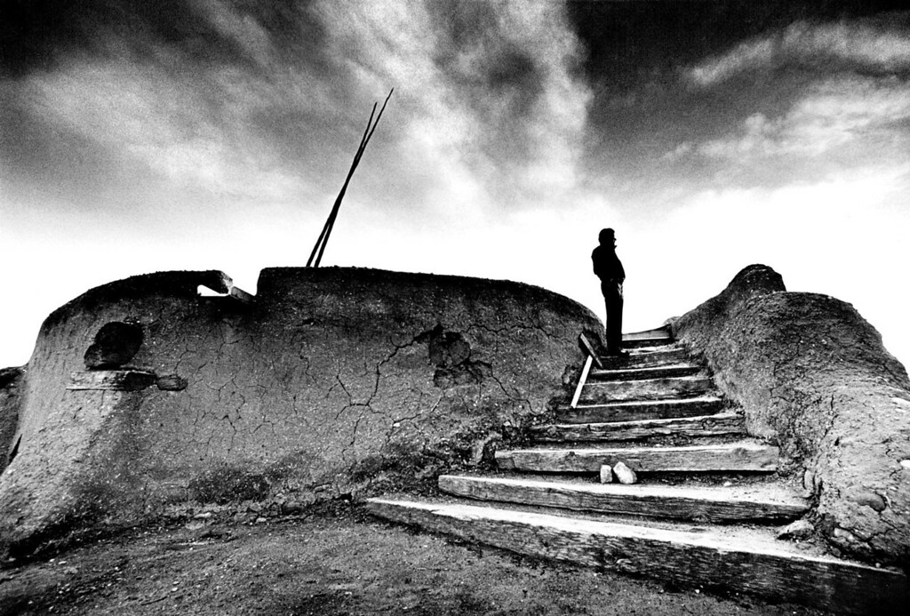 . 15 March 1987.  With love, they say in the Southwest, adobe will last forever. Standing at the top of the steps of the round adobe Kiva his ancestors started in the 13th Century, Nambe Tribal Councilman Gilbert Pena looks out over the village at sunset. The visible adobe walls enclose the upper half of the secret ceremonial chamber which can be entered only by ladder through a hole in the roof.   (From The Denver Post Archive)