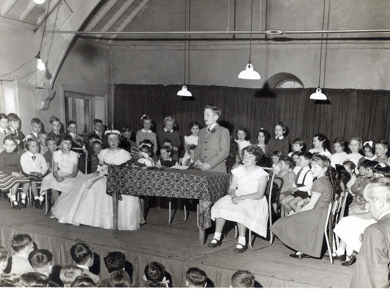 Graham Edge as Bazaar Chairman, in the old school, The headmaster Mr Watson is at the front right corner.