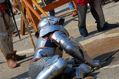 Knights in real plate armour and with real iron swords combating. This knight is floored. Impressive to hear the sound of the crossing swords and the swords touching the body harness. At times the fights were very rude! It's all part of the events happening in the medieval village at the Place du Grand Sablon (Zavel) in Brussels, Belgium, during the Ommegang festivities.