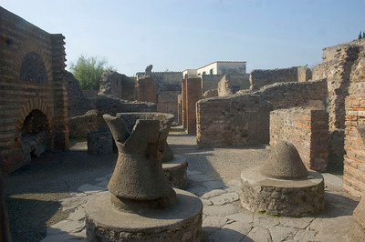 Pistrinum, or bakery in Pompeii, showing both the grinding mills of volcanic rock and one of the large wood-fired ovens.