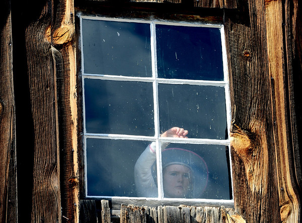 "Sadie Van Konynenberg, 6, peeks out an upstairs window of one of the Walker Ranch houses.<br /> Walker Ranch celebrated Autumn with a demonstration of life in the 1880's and a vintage baseball game on Sunday.<br /> For more photos and a video of Walker Ranch, go to  <a href=""http://www.dailycamera.com"">http://www.dailycamera.com</a>.<br /> Cliff Grassmick  / September 30, 2012"
