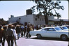 3*Sat, Aug 16, 1969<br /> *People: crowd<br /> Subject: Lucky supermarket<br /> *Place: Walnut Creek<br /> Activity:  tour of suburbia<br /> Comments: huge car, one lone strugglng tree, freaky hair, shirt