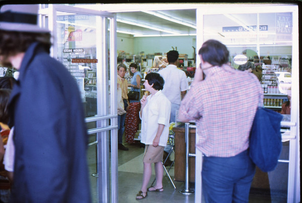 "3*Sat, Aug 16, 1969<br /> *People: Cashier, photographer<br /> Subject: storefront<br /> *Place: shopping mall, Walnut Creek<br /> Activity: tour of suburbia<br /> Comments: customers wondering ""What's happening?"""