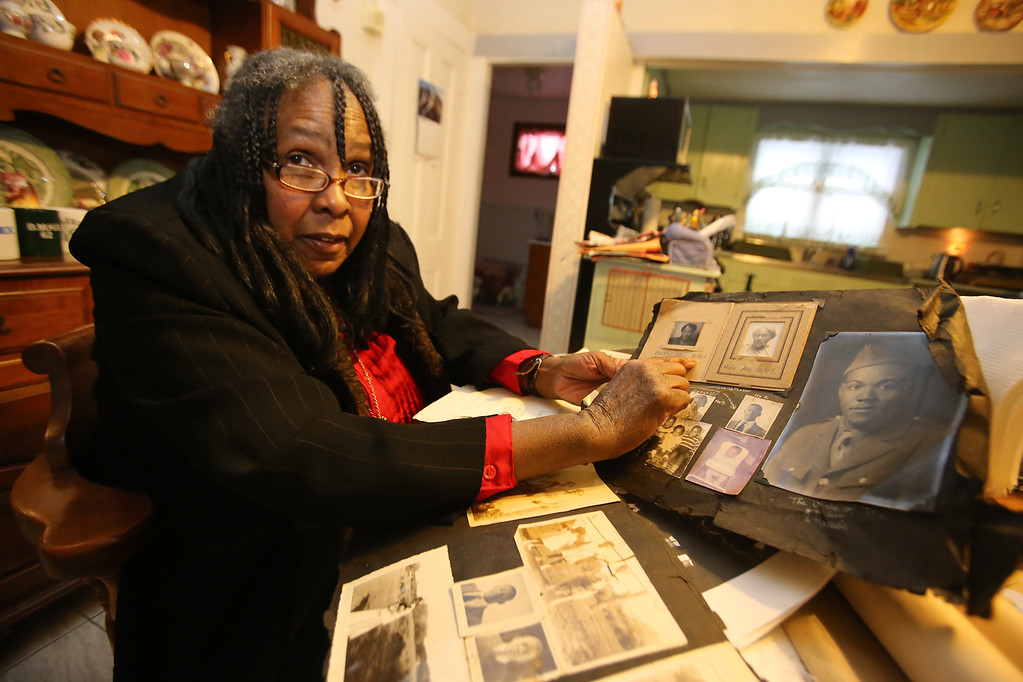 . B.J. Snowden of Billerica, with family photos of past generations of her family in Billerica. Her great-grandparents were the first black family to buy a home in Billerica. (SUN/Julia Malakie)