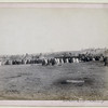 Title: Indian Council in Hostile Camp<br /> Rear view of a large semi-circle of Lakota men sitting on the ground, with tipis in background, probably on or near Pine Ridge Reservation. 1891.<br /> Repository: Library of Congress Prints and Photographs Division Washington, D.C. 20540