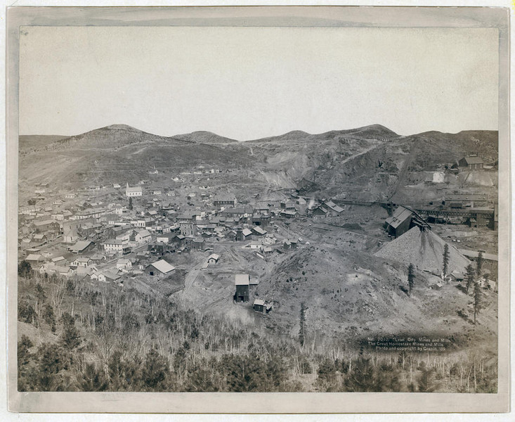 Title: Lead City Mines and Mills. The Great Homestake Mines and Mills<br /> Distant view of mining town; hills in background. 1889.<br /> Repository: Library of Congress Prints and Photographs Division Washington, D.C. 20540