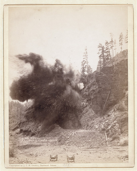 "Blasting away earth while building a railroad into Deadwood.  The photograph is dated ""90."""