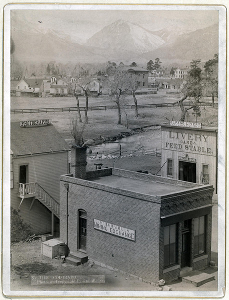 Title: Colorado<br /> Three buildings with signs reading: Grabill's Mining Exchange, Photographs, and El Paso Livery; river and houses in middleground; mountains in background. 1888.<br /> Repository: Library of Congress Prints and Photographs Division Washington, D.C. 20540