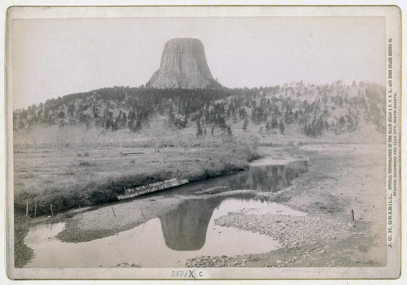 Title: Devil's Tower<br /> Distant view of Devils Tower and reflection of tower in stream in foreground. 1890.<br /> Repository: Library of Congress Prints and Photographs Division Washington, D.C. 20540