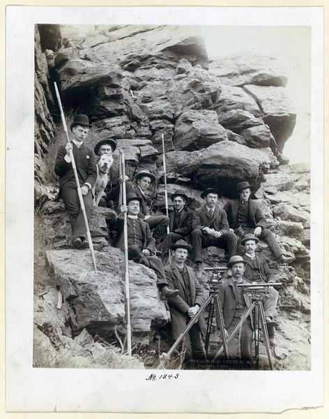Title: Deadwood Central R.R. Engineer Corps<br /> Outdoor group portrait of ten railroad engineers and a dog, posing with surveyors' transits on tripods and measuring rods, on the side of a mountain. Most of the men are sitting; all are wearing suits and hats. [1888]<br /> Repository: Library of Congress Prints and Photographs Division Washington, D.C. 20540