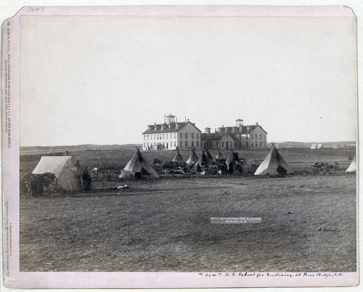 Title: U.S. School for Indians at Pine Ridge, S.D.<br /> Small Oglala tipi camp in front of large government school buildings in open field. 1891.<br /> Repository: Library of Congress Prints and Photographs Division Washington, D.C. 20540