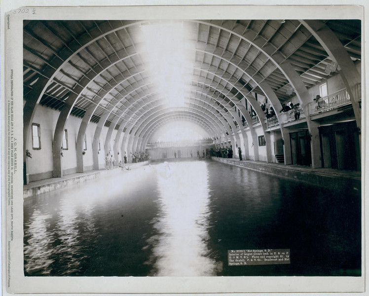 """Title: """"Hot Springs, S.D."""" Interior of largest plunge bath in U.S. on F.E. and M.V. R'y<br /> Interior view of plunge bath; bathers and spectators standing beside pool. 1891.<br /> Repository: Library of Congress Prints and Photographs Division Washington, D.C. 20540"""