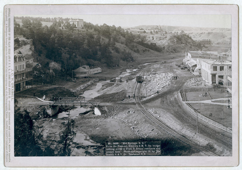 "Title: ""Hot Springs, S.D."" From the Fremont, Elkhorn and M.V. Ry. bridge looking north to Fred T. Evans residence and plunge bath<br /> Bird's-eye view of a developing small town with railroad track running through it. Large buildings on hilltops in background. 1891.<br /> Repository: Library of Congress Prints and Photographs Division Washington, D.C. 20540"