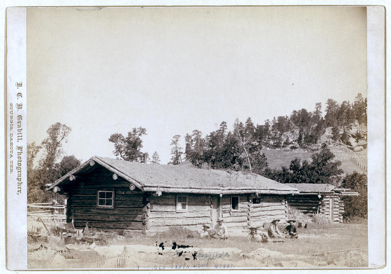 Title: The old cabin home<br /> Five men sitting in grass, in front of log cabin. [between 1887 and 1892]<br /> Repository: Library of Congress Prints and Photographs Division Washington, D.C. 20540