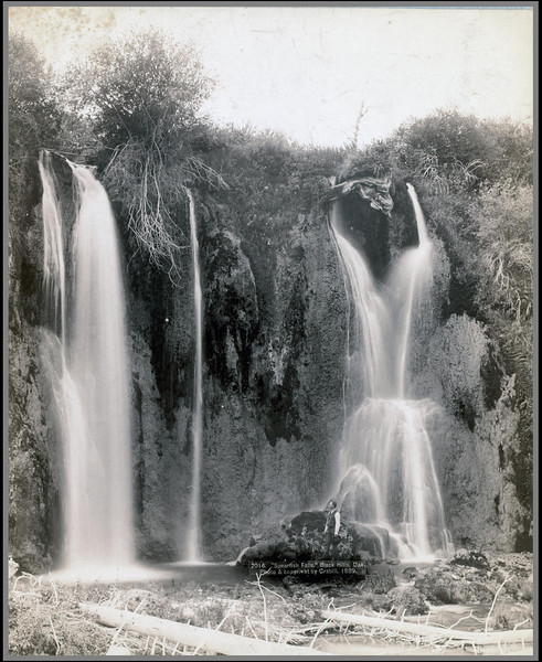 "Title: ""Spearfish Falls."" Black Hills, Dak.<br /> Man standing below two waterfalls. 1889.<br /> Repository: Library of Congress Prints and Photographs Division Washington, D.C. 20540"