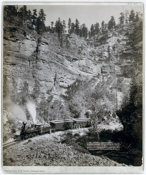 """Giant Bluff"" in Elk Canyon on Black Hills and Ft. P. R.R.  A two-car train in front of a steep cliff; several passengers are posing in front of the train. 1890. This John Grabill photo resides in the Library of Congress.  It's typical of the many dozens of photographs Reed Richards shared with LCHS members."