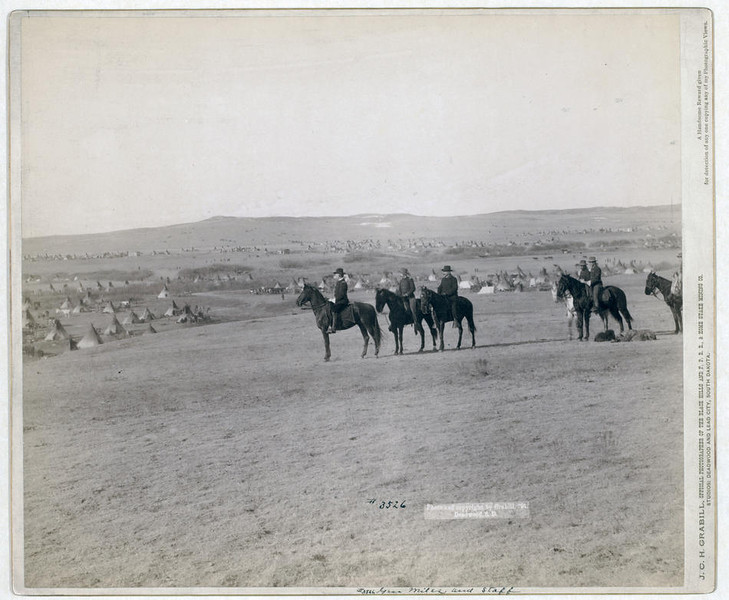 Title: General Miles and staff<br /> Six military men on horseback on a hill overlooking a large encampment of tipis. 1891.<br /> Repository: Library of Congress Prints and Photographs Division Washington, D.C. 20540