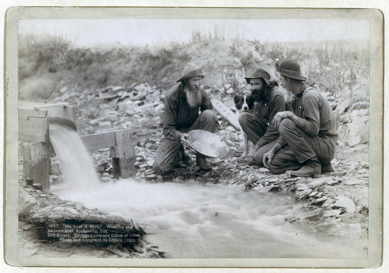 """Title: """"We have it rich."""" Washing and panning gold, Rockerville, Dak. Old timers, Spriggs, Lamb and Dillon at work<br /> Three men, with dog, panning for gold in a stream. 1889.<br /> Repository: Library of Congress Prints and Photographs Division Washington, D.C. 20540"""