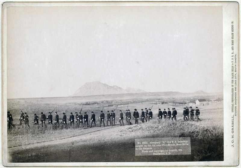 "Title: Company ""C,"" 3rd U.S. Infantry, caught on the fly, near Fort Meade. Bear Butte in the distance<br /> Thirty five soldiers walking in a line with rifles. 1890.<br /> Repository: Library of Congress Prints and Photographs Division Washington, D.C. 20540"