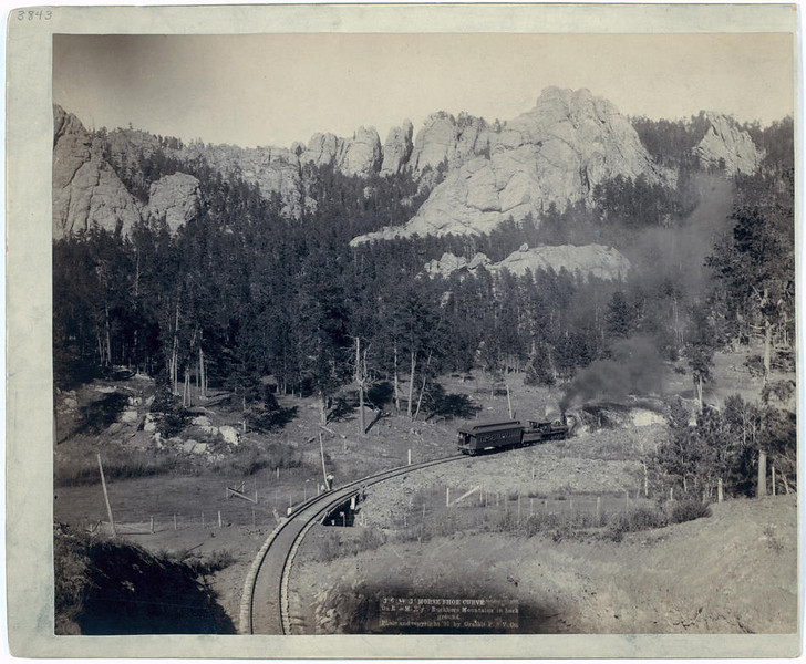 "Title: ""Horse Shoe Curve."" On <b><i>B&MR</i></b> [Burlington and Missouri River]<b><i> R'y</i></b>. Buckhorn Mountains in background.  Bird's-eye view of a train on tracks, just beyond a marked curve. 1891. Repository: Library of Congress Prints and Photographs Division Washington, D.C. 20540"