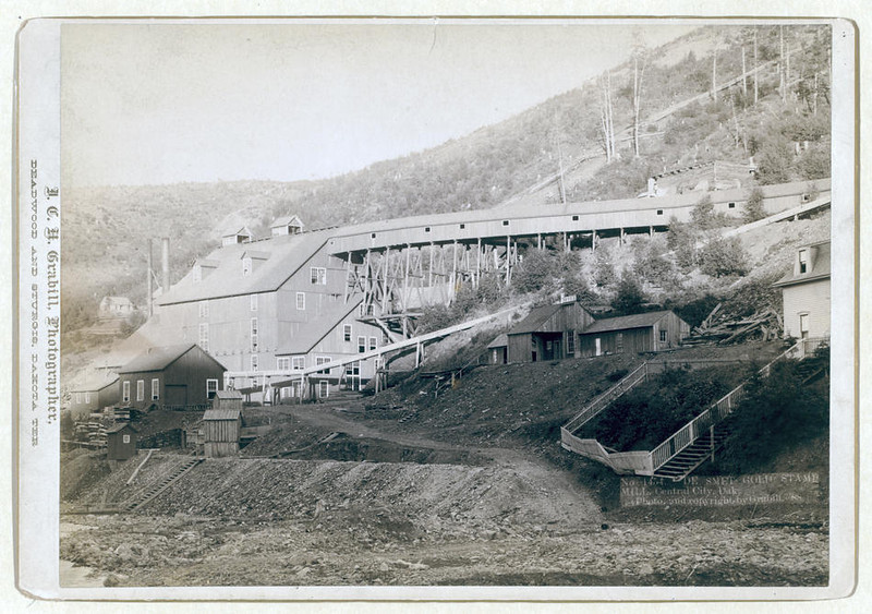 Title: De Smet Gold Stamp Mill, Central City, Dak.<br /> Large mill; five smaller buildings in foreground. 1888.<br /> Repository: Library of Congress Prints and Photographs Division Washington, D.C. 20540