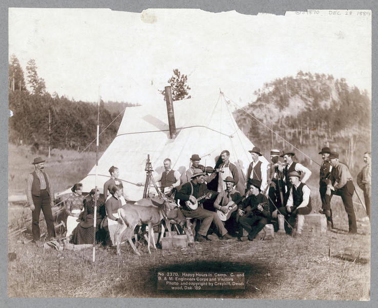 Title: Happy Hours in Camp. G. and B.&M. Engineers Corps and Visitors<br /> Small group of men and women and two deer in front of a tent. Some of the men are playing musical instruments. 1889.<br /> Repository: Library of Congress Prints and Photographs Division Washington, D.C. 20540