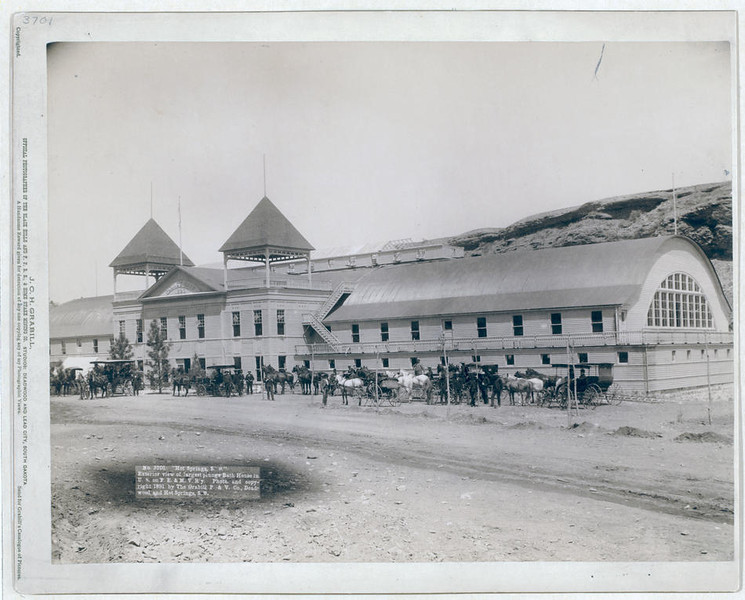 """Title: """"Hot Springs, S.D."""" Exterior view of largest plunge bath house in U.S. on F.E. and M.V. R'y<br /> Large building with several horses and carriages in front. 1891.<br /> Repository: Library of Congress Prints and Photographs Division Washington, D.C. 20540"""