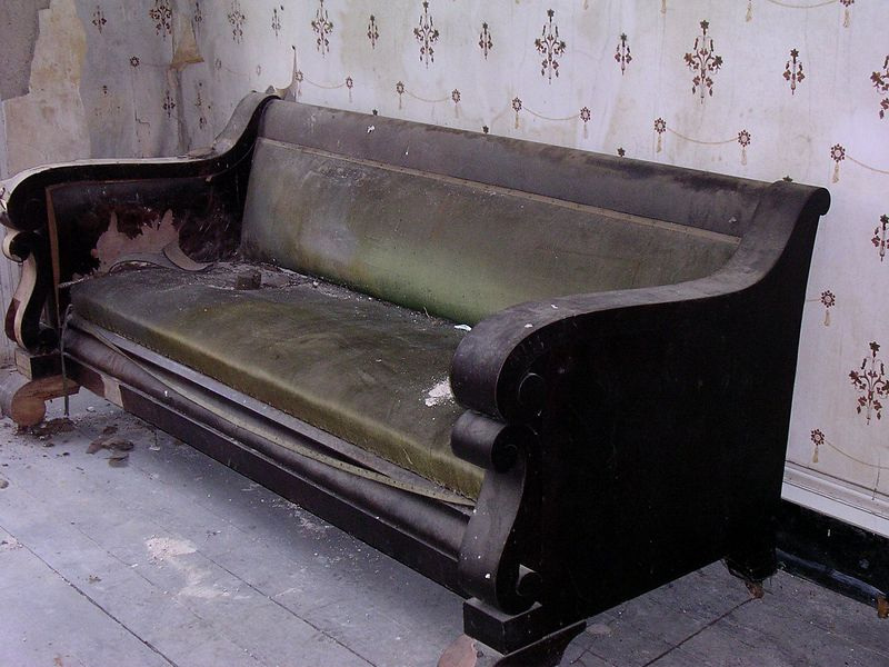 An elegant old green-velvet sofa sits alone amid the dust in the second floor main hall.