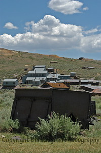 A massive old ore cart with the mine complex on the hillside in the background.