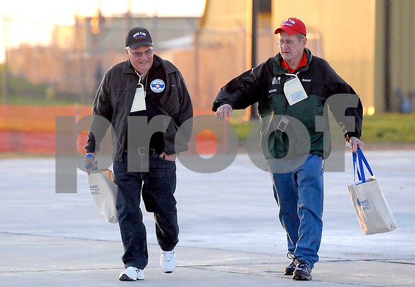-Messenger photo by Hans Madsen<br /> <br /> Korean War Navy veteran Bob Boeger, of Fort Dodge, right, along with his guardian, Richard Lawson, of Fort Dodge, brave the wind Saturday morning to walk from the hangar to the airplane.