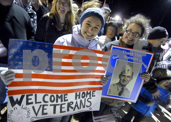 -Messenger photo by Hans Madsen<br /> <br /> Sydney O'Leary, of Naperville, Ill., and Katie Larson, of Wheaton, Ill., hold up signs Saturday night at the Fort Dodge Regional Airport to welcome Korean War veteran Norman Larson, of Badger, back home after the Brushy Creek Area Honor Flight to Washington D.C.  Larson is O'Leary's great-uncle and Larson's grandfather.