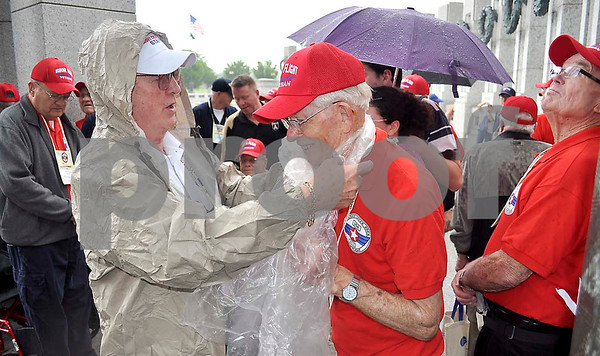 -Messenger photo by Jesse Helling<br /> <br /> Ron Newsum, director of the Brushy Creek Honor Flight, helps Army veteran Maurice Nolte on with a poncho at the World War II Memorial.