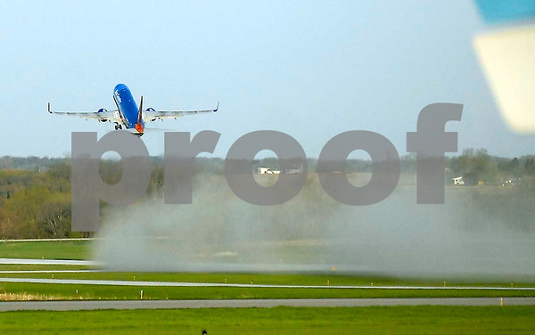 -Messenger photo by Hans Madsen<br /> <br /> The exhaust from the Sun Country jet cleans the dust, dirt and sand from the runway Saturday morning as the Brushy Creek Area Honor Flight takes off from the Fort Dodge Regional Airport.