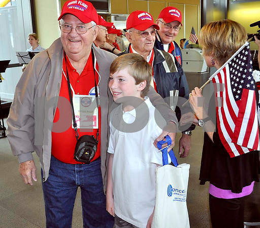-Messenger photo by Jesse Helling<br /> Sherman Silbaugh pauses for a photo with Aidan Pollard, a fourth-grader from clifton, Va. Pollard was part ofthe welcoming group that greeted veterans of the Brushy Creek Area Honor Flight upon their arrival at Dulles International Airport in Washington D.C.
