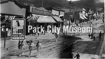 A parade on Main Street: American Showhouse-/ Golden Rule/ Haraus Saloon/ Bobs Cafe/ Maple Hall Site/ Green Front Saloon/ White Front Saloon/ Rasband Butcher Shop/ Davich Bldg/ Rasband Hall/ circa 1910's (Image: 1999-17-103; Fraser Buck Collection)