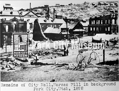 "Main Street after the Great Fire looking east featuring the remains of City Hall, the First National Bank, and Marsac Mill. Underneath the image are the words ""Remains of City Hall, Marsac Mill in background/ Park City, Utah, 1898"". (Image: 2007-11-36B, Thomas F. Hansen Collection)"