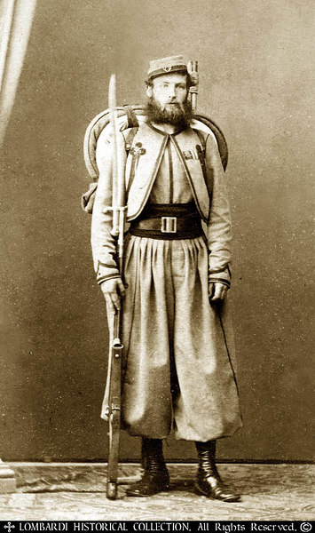 Ca.1865 CDV of a Pontifical Zouave. A decorated Volunteer who served in Major O'Reilley's Papal Brigade and veteran of the battles against Garibaldi.  Fully armed and equipped with a  .71 cal. Model 1842 French Rifle with sword bayonet, backpack with blanket and the Pope's Cross Ribbon decoration.  Photographer, Fratelli D'Alessandri, Roma