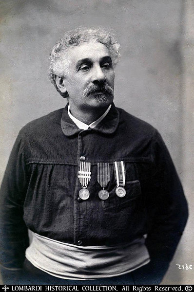 """One of a Thousand"".Ca. 1890 photograph of a proud Veteran of Garibaldi's Red Shirt Volunteers, Burano Bedeschini (personally signed by him), posing with his original red shirt and decorations of the Risorgimento"