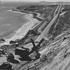 Two-yard power shovel removing 50,000 cubic yards deposit of beach sand on a bench 90 feet above coast highway