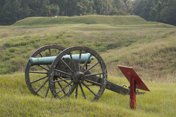 A Confederate cannon in the foreground with a Confederate fort, Fort Garrott, in the background, on the siege-line at Vicksburg National Military Park.