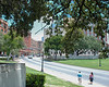 """View from the grassy knoll, kill shot impacted at the """" X """" in center of Elm st. Snipers nest can be seen in upper left, window open."""