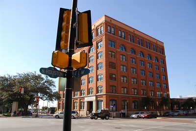 The old Texas School Book Depository from the corner where the limo passed just before the shooting.  The limo was heading from right to left and the grassy knoll is just to the left of the big tree.