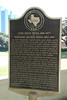 Placard near the grassy knoll. Roll your pointer over pic and choose X2Large and it becomes readable.